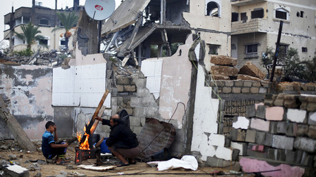 Palestinians use wood to light a fire inside the ruins of their house, that witnesses said was destroyed by Israeli shelling during a 50-day war in the summer of 2014, on a rainy day in Gaza city © Suhaib Salem