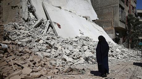 A woman walks past a damaged building after an airstrike in the rebel held Douma neighbourhood of Damascus, Syria. ©Bassam Khabieh
