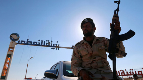 A member of Libyan forces loyal to eastern commander Khalifa Haftar holds a weapon as he sits on a car in front of the gate at Zueitina oil terminal in Zueitina, west of Benghazi, Libya. © Esam Omran Al-Fetori