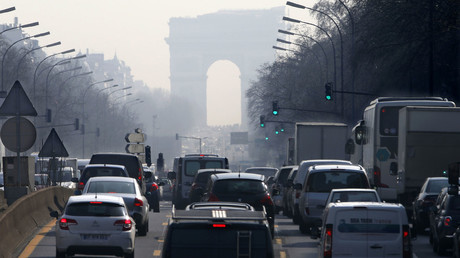 Rush hour traffic fills an avenue leading up to the Arc de Triomphe which is seen through a small-particle haze at Neuilly-sur-Seine, Western Paris © Charles Platiau