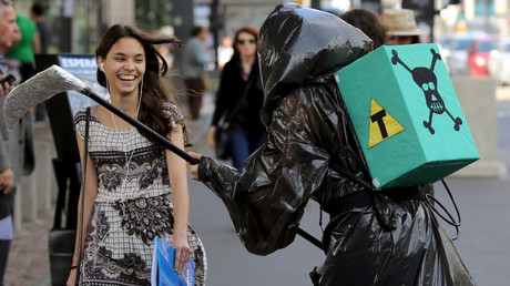 A woman reacts to an activist carrying a box with a transgenic symbol during a protest against Monsanto in Brazil © Paulo Whitaker