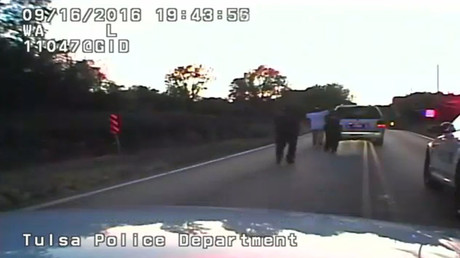 A still image captured from a dashcam video from Tulsa Police Department shows Terence Crutcher seen with his hands in the air followed by police officers during a police shooting incident in Tulsa, Oklahoma, U.S. on September 16, 2016. Video taken September 16, 2016. © Tulsa Police Department