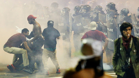 People maneuver amongst tear gas in uptown Charlotte, NC during a protest of the police shooting of Keith Scott, in Charlotte, North Carolina, U.S. September 21, 2016 © Jason Miczek