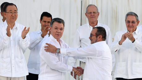 "Colombian President Juan Manuel Santos and rebel leader Rodrigo Londono, aka Timoleon ""Timochenko"" Jimenez, shake hands as they sign a historic peace treaty between the government and the Revolutionary Armed Forces of Colombia (FARC) in Cartagena, Colombia. © Luis Acosta"