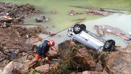 A rescue worker is seen next to an overturned car at the site of a landslide caused by heavy rains brought by Typhoon Megi, in Sucun Village, Lishui, Zhejiang province, China, September 29, 2016 © Stringer