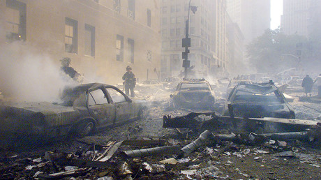 Cars smolder in the street as the destroyed World Trade Center burns in New York on September 11, 2001 © Reuters