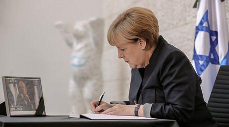 German Chancellor Angela Merkel sings a book of condolence for former Israeli President Shimon Peres at the embassy of Israel in Berlin, Germany, September 30, 2016 © Michael Kappeler