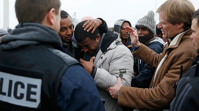 "Pascal Brice (R), the head of OFPRA, French Office for Refugees and Stateless Persons, comforts an Ethiopian migrant, as he leaves the Calais ""Jungle"" to be transferred to reception centers, in Calais, France, October 24, 2016. © Pascal Rossignol"