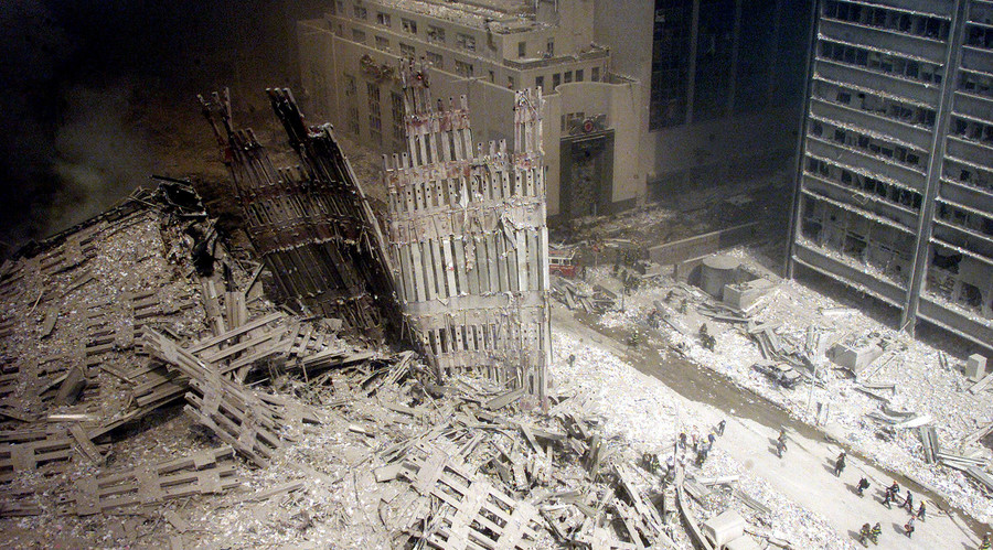 A group of firefighters walk amid rubble near the base of the destroyed