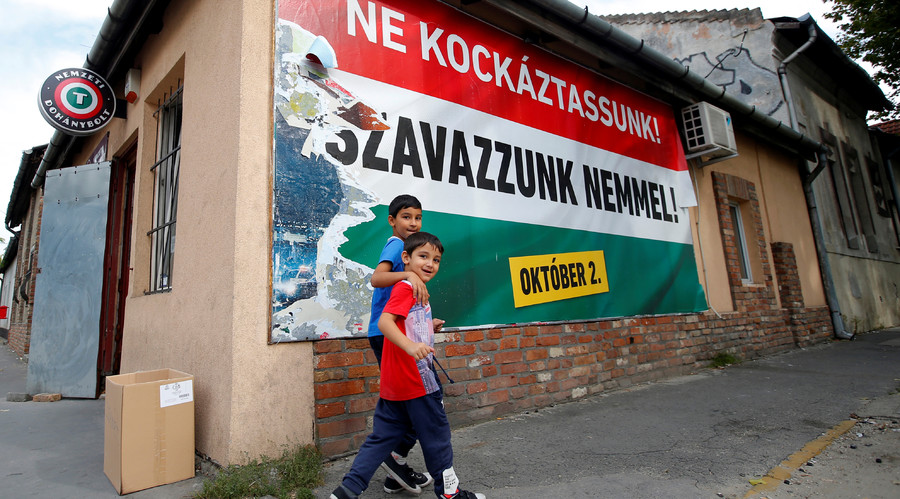 Hungarian Roma boys walk in front of the Hungarian goverment's poster regarding referendum on EU migrant quotas in Budapest, Hungary, September 28, 2016. © Laszlo Balogh