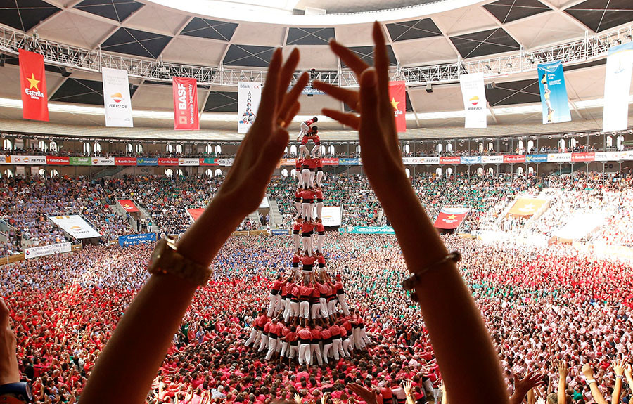 "Colla Vella Xiquets de Valls form a human tower called ""castell"", while a supporter applauds, during a biannual competition in Tarragona city, Spain, October 2, 2016. © Albert Gea"