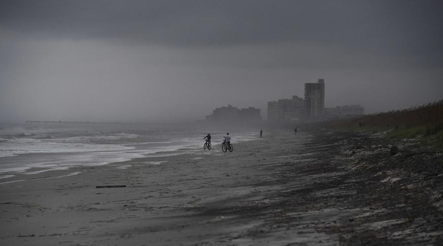 People bike on the beach ahead of hurricane Matthew in Atlantic Beach, Florida, on October 5, 2016 © Jewel Samad