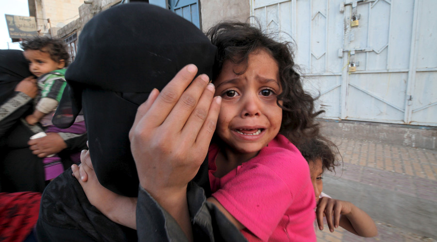 A girl cries next to her mother covering her face as they flee from an airstrike on an army weapons depot in Yemen's capital Sanaa. File photo. © Mohamed al-Sayaghi