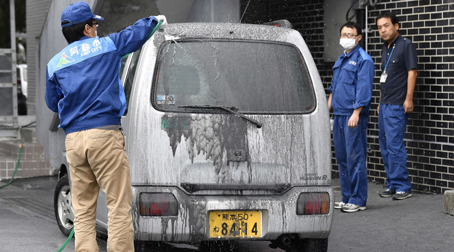 An officer of the city government cleans a car covered in volcanic ash which came from the eruptive crater of Mount Aso in Aso, Kumamoto prefecture, southwestern Japan © Kyodo