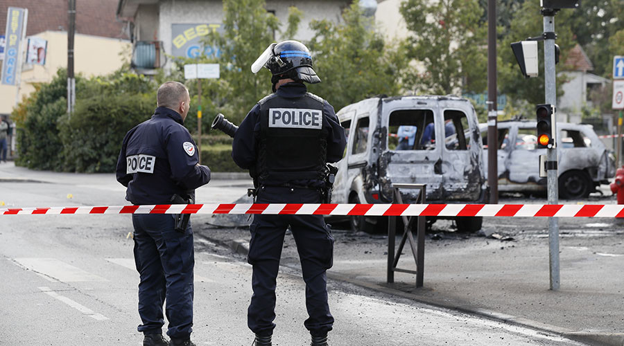 Police stand guard near a burned police vehicle (R) and a van in Viry-Chatillon on October 8, 2016 after police in their patrol car were attacked by individuals who launched Molotov cocktails, leaving two officers injured. ©Thomas Samson