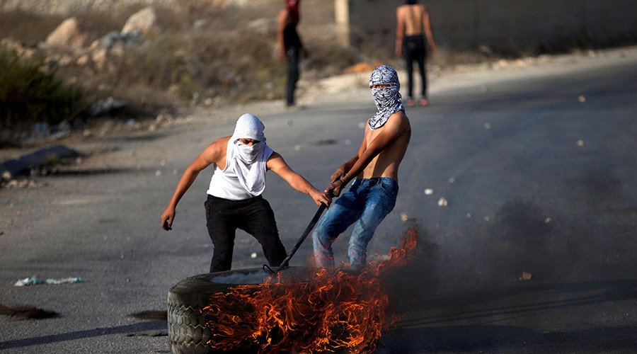 Palestinian protesters drag a burning tyre during clashes with Israeli troops © Mohamad Torokman