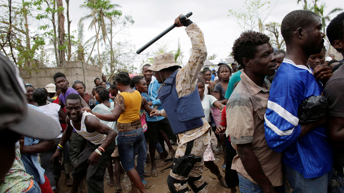 A Haitian national police officer keeps people away during distribution of supplies after Hurricane Matthew in Torbeck, Haiti, October 19, 2016. © Andres Martinez Casares