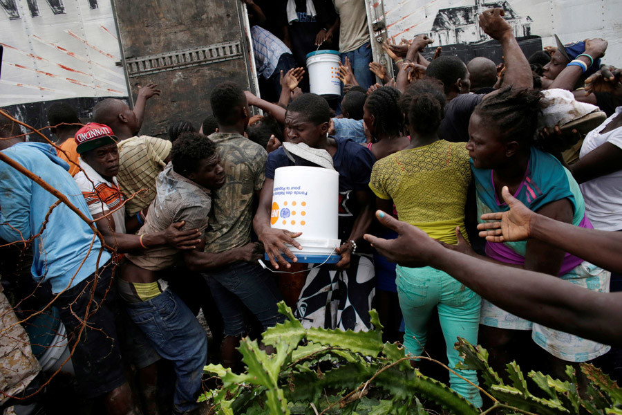 People fight over a bucket of supplies after Hurricane Matthew in Torbeck, Haiti, October 19, 2016. © Andres Martinez Casares