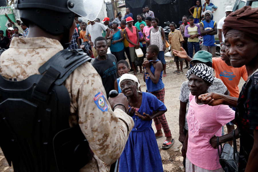 A woman talks to a police officer during distribution relief after Hurricane Matthew hit Jeremie, Haiti, October 19, 2016. © Carlos Garcia Rawlins