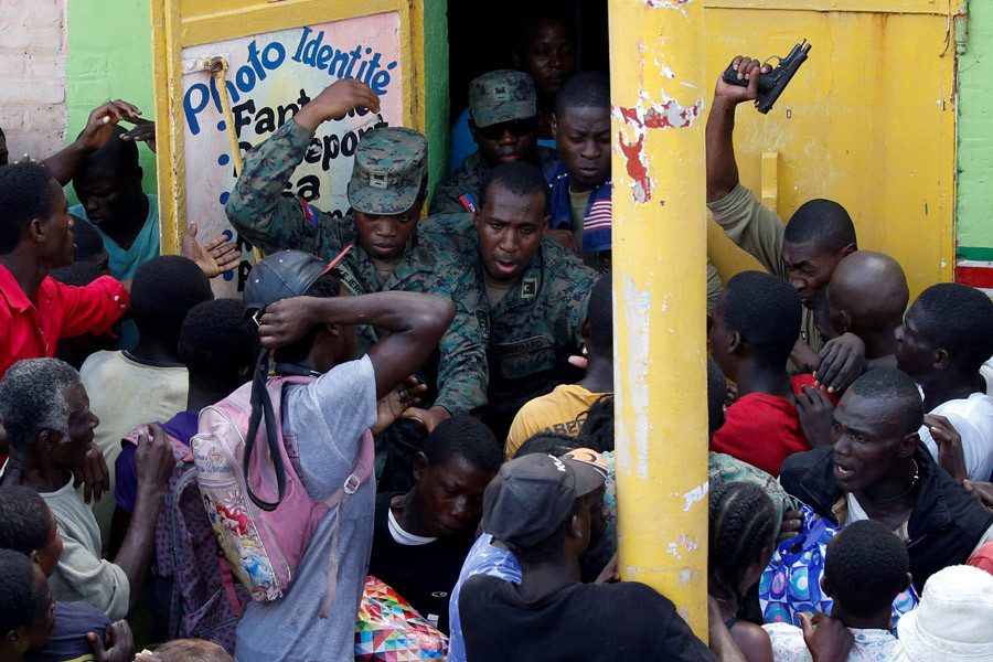 Haitian soldiers shoot in the air to try to control the crowd as they wait for food distribution after Hurricane Matthew hit Jeremie, Haiti, October 18, 2016. © Carlos Garcia Rawlins