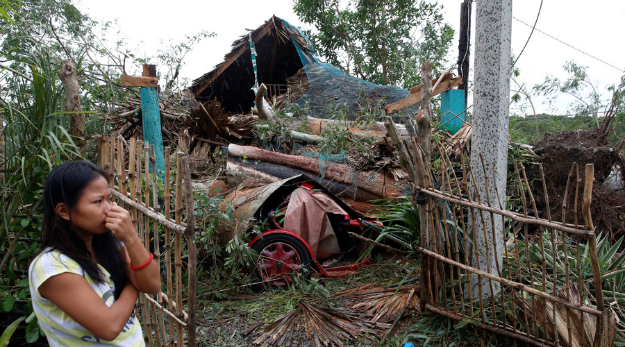 A woman stands outside her house which was damaged by a fallen tree during Typhoon Haima, in Bangui, Ilocos Norte in northern Philippines, October 20, 2016. © Erik De Castro