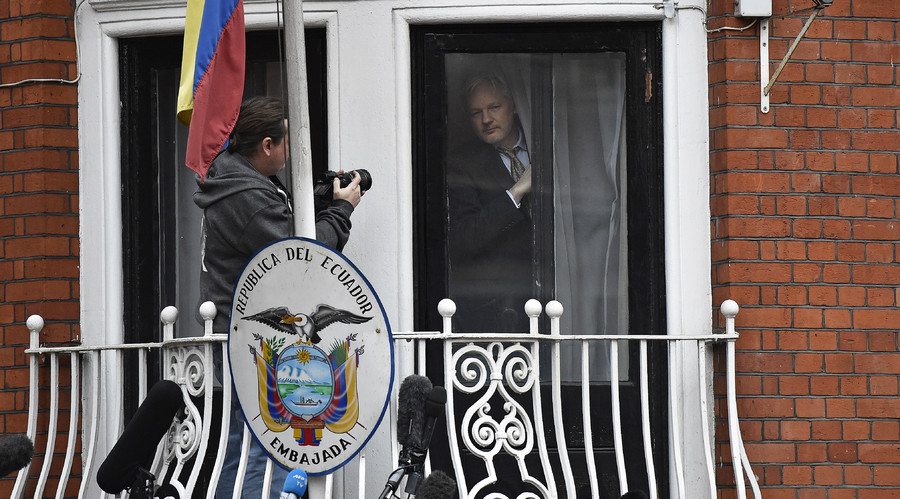 WikiLeaks founder Julian Assange peers out from behind a curtain before emerging to make a speech from the balcony of the Ecuadorian Embassy, in central London, Britain February 5, 2016. © Toby Melville