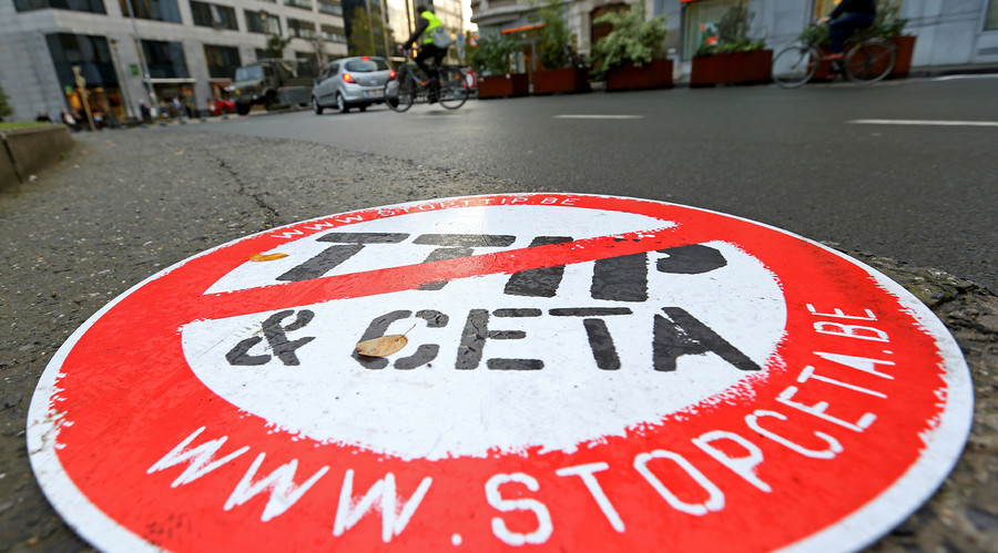 "A cyclist rides past a placard reading "" STOP TTIP CETA"" outside the EU Council headquarters ahead of a European Union leaders summit in Brussels, Belgium © Yves Herman"