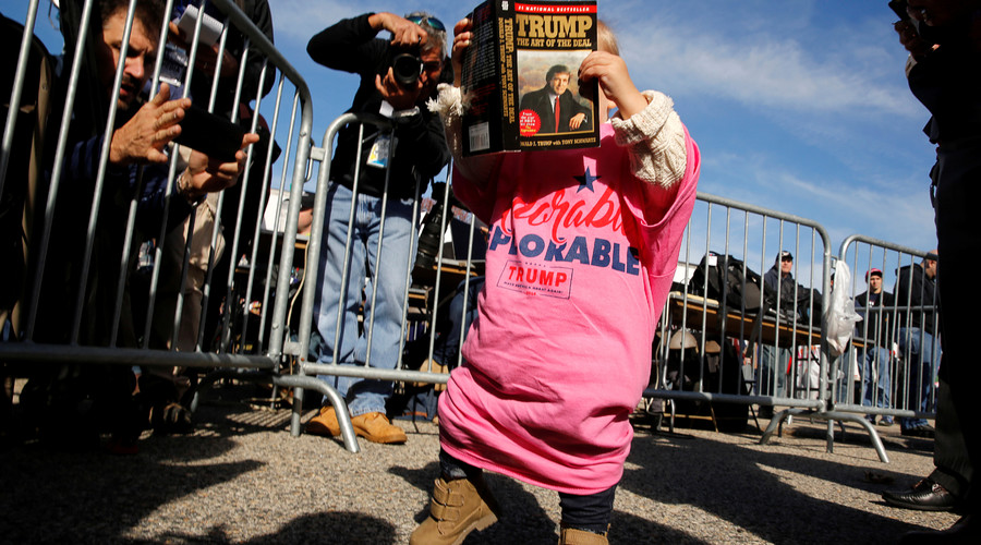 Photographers take pictures of a toddler with a book by Republican presidential nominee Donald Trump as they wait for the start of a rally with him at a car dealership in Portsmouth, New Hampshire, U.S. October 15, 2016. © Jonathan Ernst