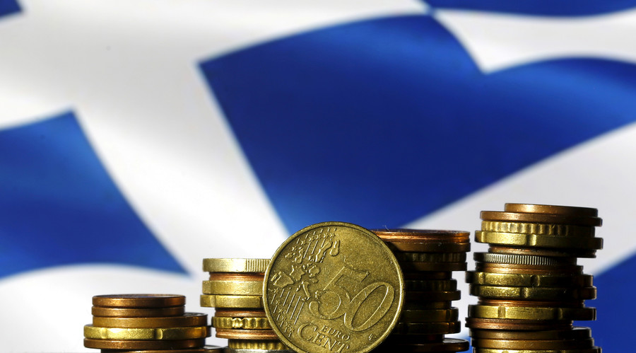 Euro coins are seen in front of a displayed Greece flag © Dado Ruvic
