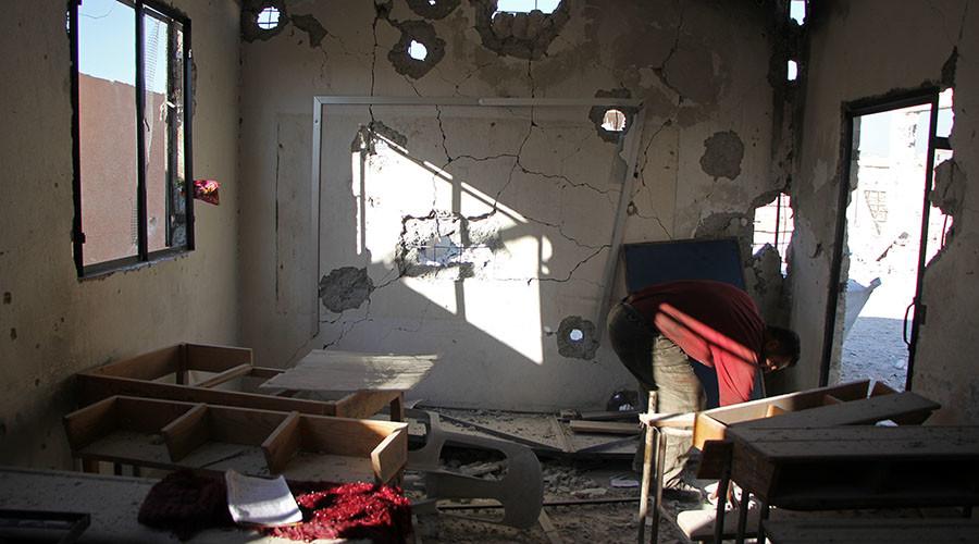 رجل سوري يتحقق الضرر في المدرسة بعد أن عصفت به في غارة جوية مزعومة في قرية هاس، في الجنوب من محافظة إدلب التي يسيطر عليها المتمردون في سوريا في 26 أكتوبر، 2016. © عمر الحاج قدور