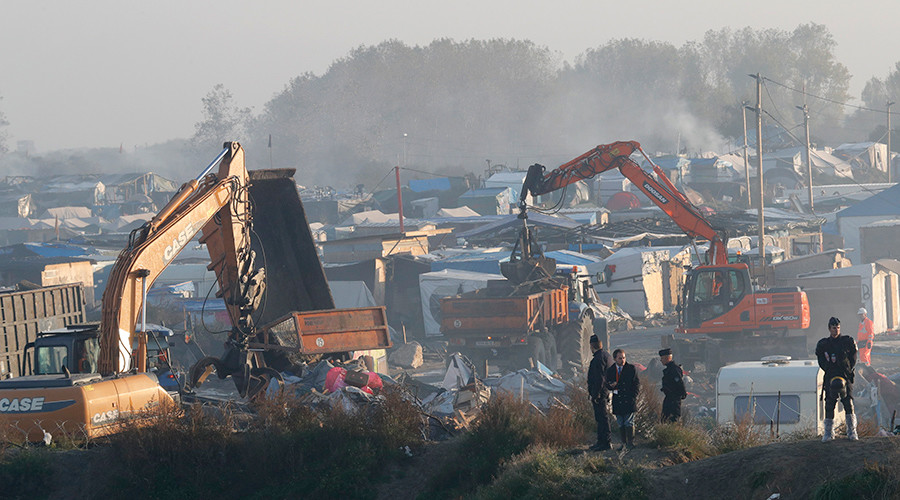 """Bulldozers are used to remove debris as workmen tear down makeshift shelters during the dismantlement of the camp called the """"Jungle"""" in Calais, France, October 27, 2016 © Philippe Wojazer"""