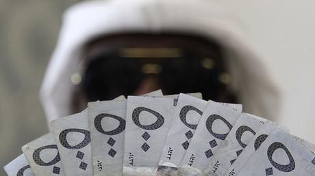 Un hombre posa con Arabia billetes Riyal saudí.  © Faisal Al Nasser