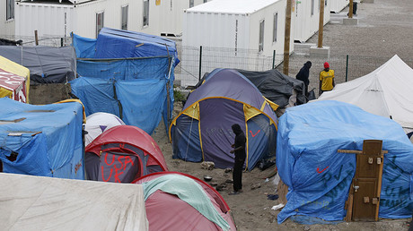 Migrants stand up outside their shelters in the northern area of the camp called the