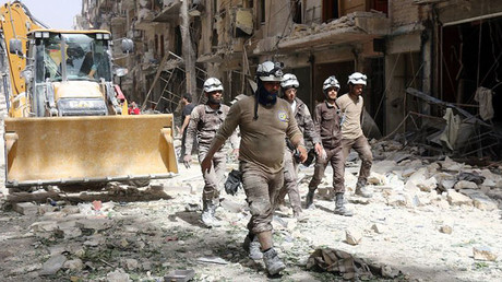 The White Helmets walk amid the debris in a rebel-held neighbourhood of Aleppo. © Thaer Mohammed