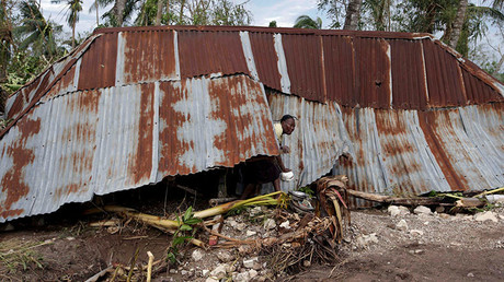 A woman gets out of a house destroyed by Hurricane Matthew in Cavaillon, Haiti, October 6, 2016. © Andres Martinez Casares