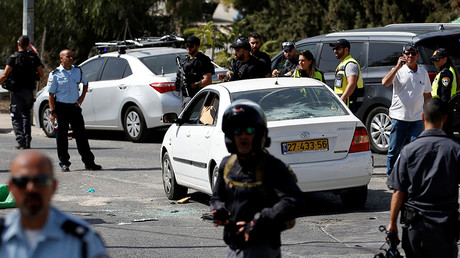 Israeli police and emergency personnel stand next to a car covered with bullet holes after Israeli police killed an Arab assailant who fired from the car wounding several people in Jerusalem October 9, 2016 © Ronen Zvulun