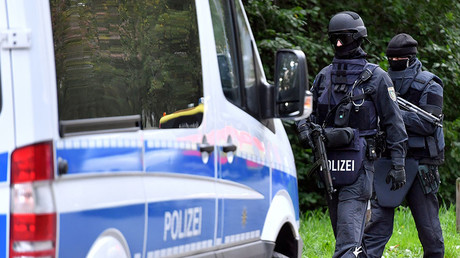 Policemen of a special unit are pictured at the Yorckgebiet district of Chemnitz, eastern Germany, where German police commandos hunting a fugitive Syrian bomb plot suspect raided a flat on October 9, 2016. © DPA