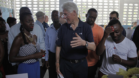 Former U.S. President Bill Clinton (C) chats with staff members during a tour to Kreyol Essence, a Haitian women owned and operated company in Mirebalais February 23, 2015 © Andres Martinez Casares