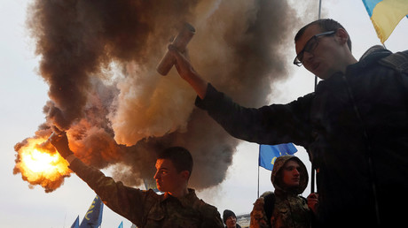 Activists hold smoke flares as they take part in a rally held by far-right radical groups, including All-Ukrainian Union Svoboda (Freedom), to mark Defender of Ukraine Day, in Kiev, Ukraine, October 14, 2016. © Valentyn Ogirenko