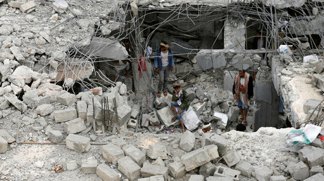 A man sits near others amidst rubble of a building destroyed in the northwestern city of Amran, Yemen. © Khaled Abdullah