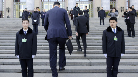Former NBA basketball player Yao Ming (2nd L) walks past security personnel as he arrives for the closing session of the Chinese People's Political Consultative Conference (CPPCC) outside the Great Hall of the People, in Beijing © Jason Lee