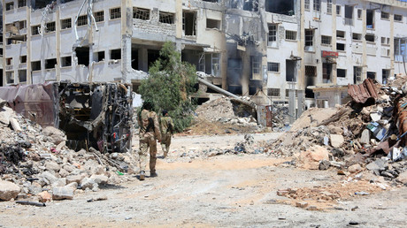Forces loyal to Syria's President Bashar al-Assad walk past rubble, the southern side of the Castello road in Aleppo, Syria. © SANA