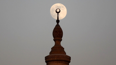 The full Moon rises over a minaret of a mosque during sunset. © Amr Abdallah Dalsh