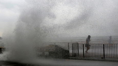 People run away from a big wave on a waterfront as Typhoon Haima approaches in Hong Kong, China, October 21, 2016 . © Bobby Yip
