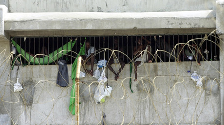 FIle photo: Prisoners at the Port-au-Prince prison look out fron behind bars © Thony Belizair