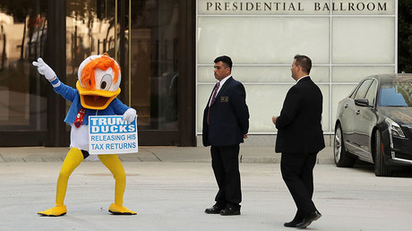 A demonstrator wearing a Donald Duck costume dances in front of the Trump International Hotel during the hotel's first day of business September 12, 2016 in Washington, DC. © Chip Somodevilla / Getty Images