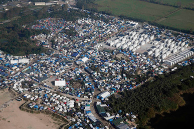 "An aerial view shows white containers, tents and makeshift shelters on the eve of the evacuation and dismantlement of the ""Jungle"" camp in Calais, France, October 23, 2016. © Pascal Rossignol"