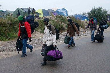 "Migrants with their belongings walk past tents at the start of their evacuation and transfer to reception centers in France, amid the dismantlement of the ""Jungle"" in Calais, France, October 24, 2016. © Pascal Rossignol"