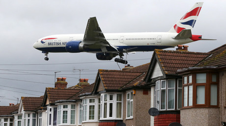An aircraft passes over houses as it lands at Heathrow Airport near London, Britain© Neil Hall