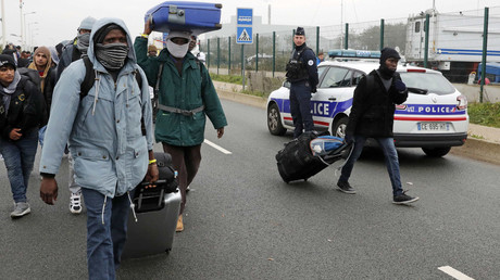 "French police stand near as migrants carry their belongings at the start of their evacuation and transfer to reception centers in France, and the dismantlement of the camp called the ""Jungle"" in Calais, France, October 24, 2016. © Philippe Wojazer"